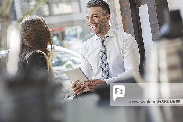 Lachender Geschäftsmann mit digitalem Tablett  der einen Kollegen in einem Café ansieht.