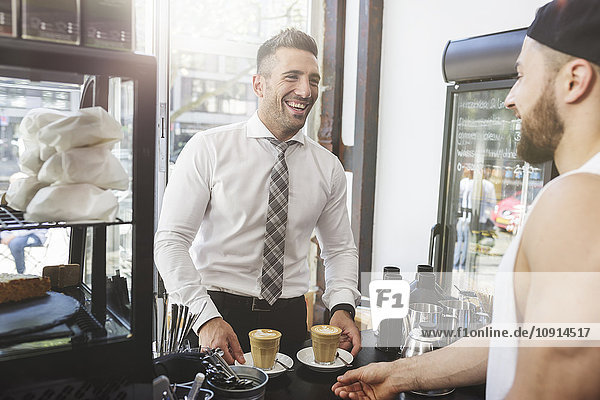 Laughing businessman in a cafe with barkeeper