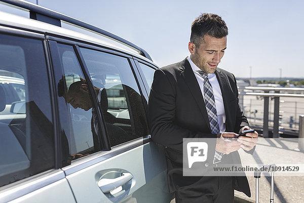 Geschäftsmann lehnt sich gegen das Auto und schaut aufs Handy