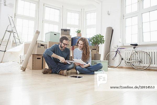 Paar umgeben von Pappkartons auf dem Boden sitzend