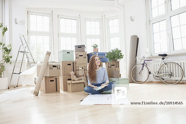 Frau umgeben von Pappkartons auf dem Boden sitzend mit Bauplan