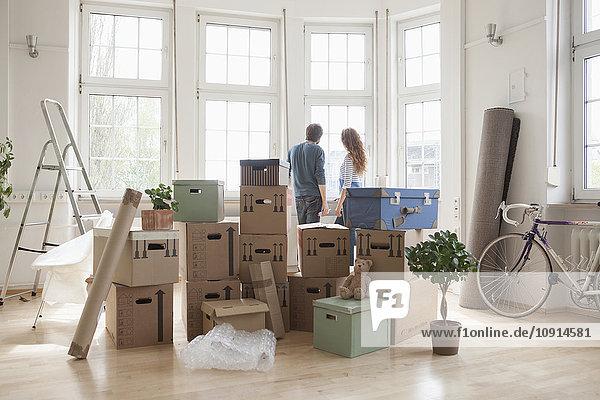 Paar mit Pappkartons in neuer Wohnung mit Blick aus dem Fenster