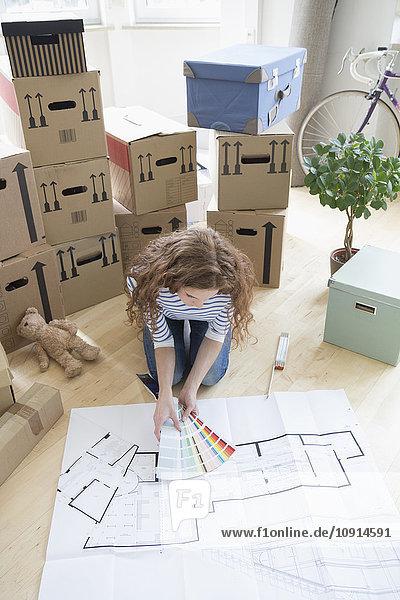 Frau umgeben von Pappkartons mit Farbmustern und Bauplan auf dem Boden Frau umgeben von Pappkartons mit Farbmustern und Bauplan auf dem Boden