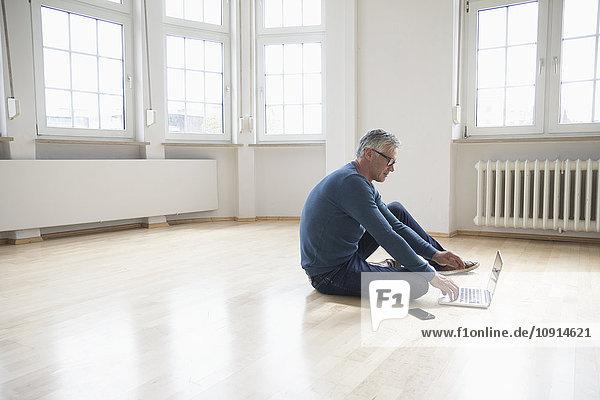 Mann mit Laptop in leerer Wohnung
