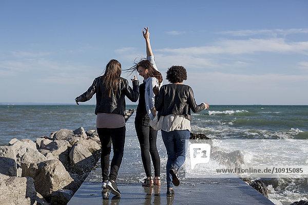 Drei junge Frauen haben Spaß auf dem Wellenbrecher am Meer