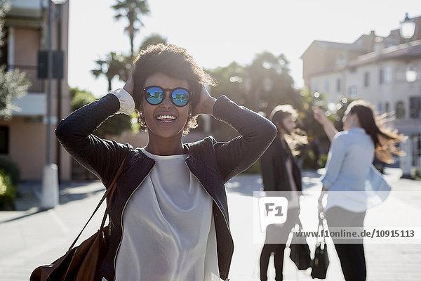 Junge Frau mit Sonnenbrille in der Stadt mit ihren Freunden