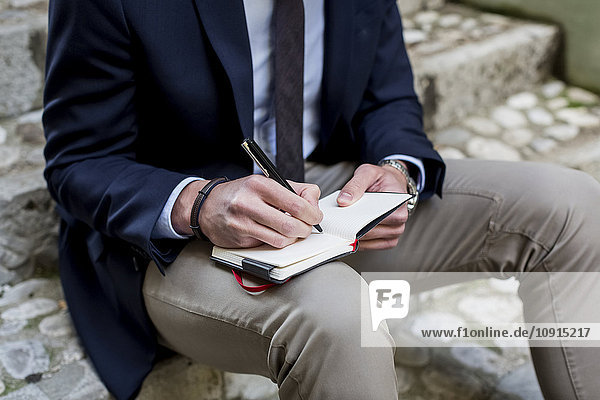 Businessman sitting on stone stairs writing in diary