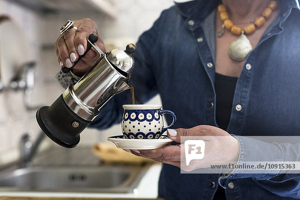 Woman pouring coffee into cup
