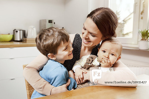 Glückliche Mutter mit ihren kleinen Söhnen in der Küche