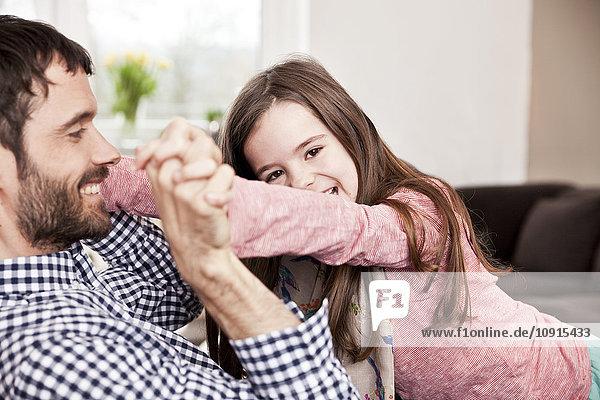 Tochter spielt mit ihrem Vater auf der Couch.