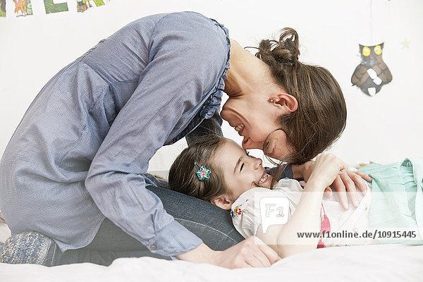 Mutter kuschelt ihre kleine Tochter zu Hause.