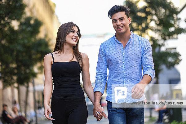 Ein glückliches junges Paar geht Hand in Hand.