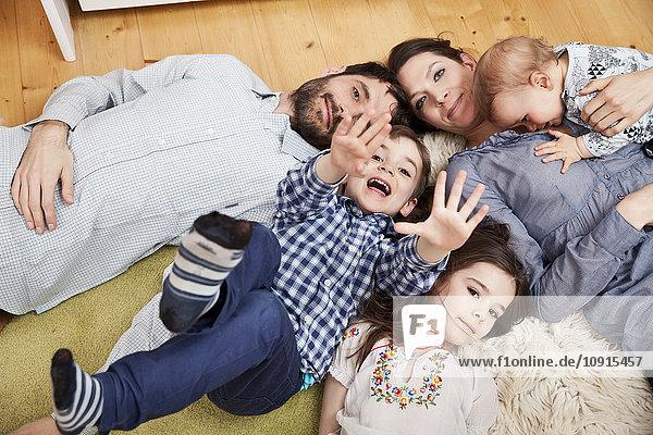 Familie mit drei Kindern  die zu Hause auf dem Boden liegen und auf die Kamera schauen.