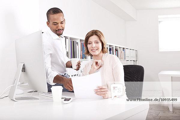 Zwei Kollegen diskutieren in einem Büro über ein Dokument