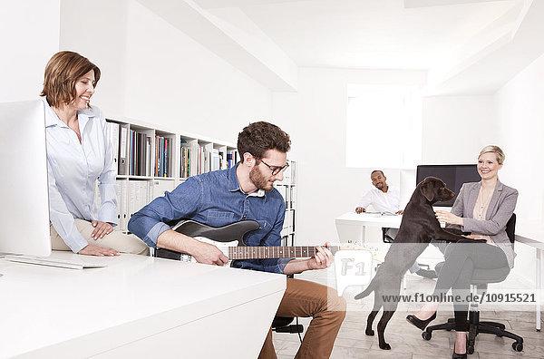 Drei Leute im Büro  die ihrem Kollegen beim Gitarrespielen zuhören.