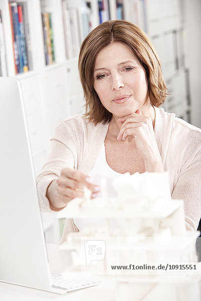Portrait of woman at desk looking at architectural model