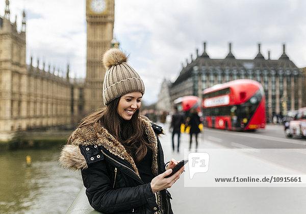 UK  London  lächelnde junge Frau schaut auf ihr Smartphone vor dem Palace of Westminster