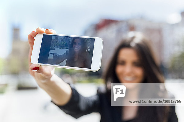 Young woman making a selfie  display of smartphone