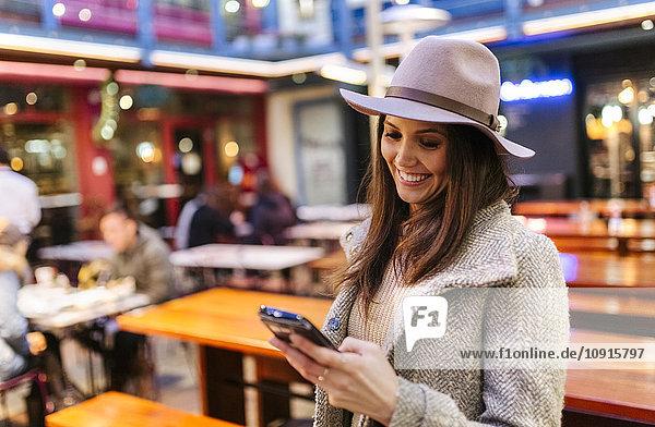 Porträt einer lächelnden jungen Frau  die ihr Smartphone ansieht.