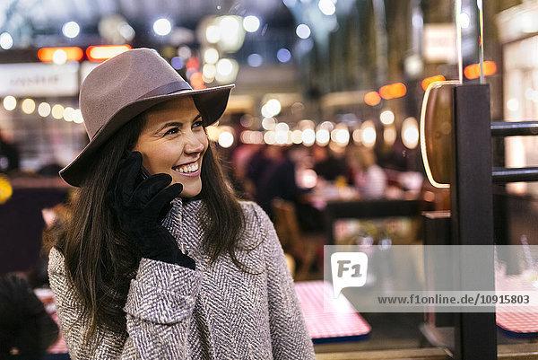 Portrait einer glücklichen jungen Frau beim Telefonieren mit dem Smartphone