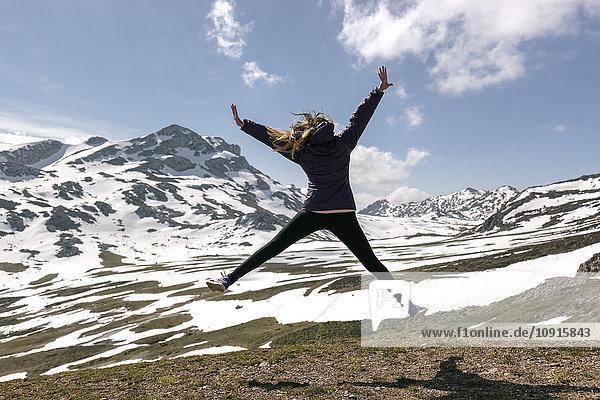 Spanien  Asturien  Somiedo  verspielte Frau beim Springen in den Bergen