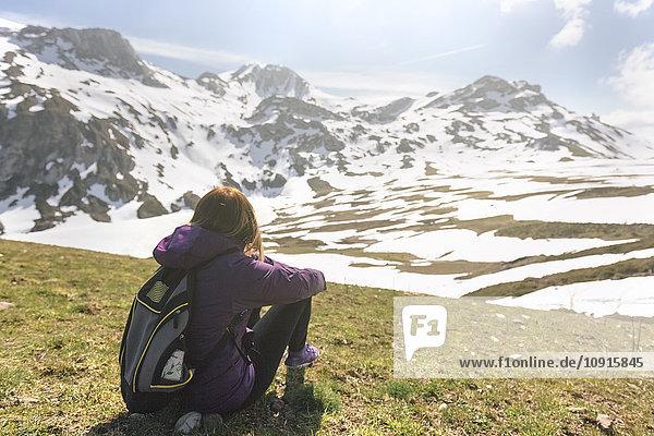 Spanien  Asturien  Somiedo  Frau mit Blick auf die Landschaft auf einer Wiese sitzend