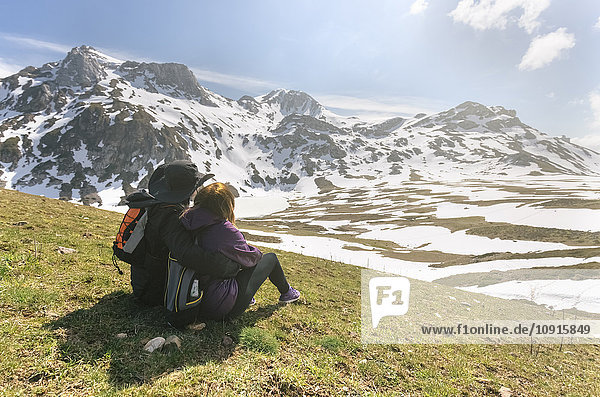 Spain  Asturias  Somiedo  couple looking at the landscape sitting in a meadow