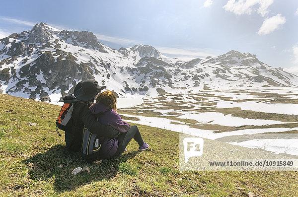 Spanien  Asturien  Somiedo  Paar mit Blick auf die Landschaft auf einer Wiese sitzend
