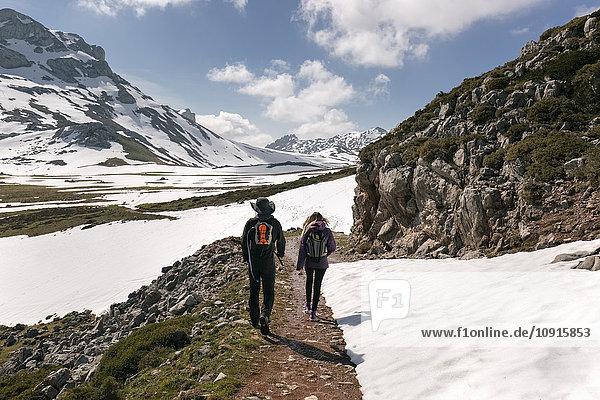 Spain  Asturias  Somiedo  couple hiking in snowy mountains