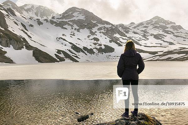 Spain  Asturias  Somiedo  woman standing at mountain lake