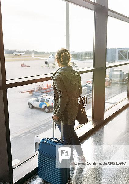 Spanien  Asturien  Frau  die mit ihrem Koffer auf dem Flughafen wartet.