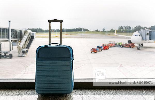 Koffer am Flughafen  Passagierflugzeug und Gepäckwagen im Hintergrund Koffer am Flughafen, Passagierflugzeug und Gepäckwagen im Hintergrund