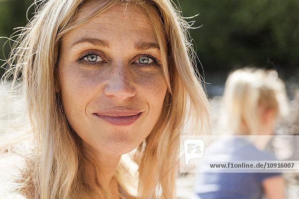 Porträt einer lächelnden blonden Frau mit Sommersprossen