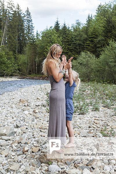Mutter und ihre kleine Tochter stehen zusammen auf einem Felsen am Flussufer.