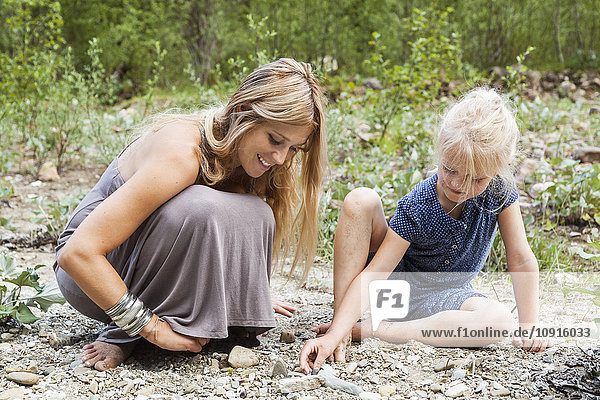 Mother and her little daughter looking for stones in nature