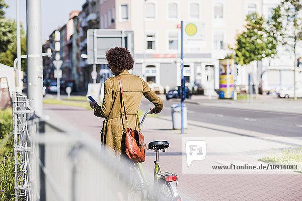 Rückansicht einer jungen Frau  die auf ihr Smartphone schaut  während sie das Fahrrad schiebt.