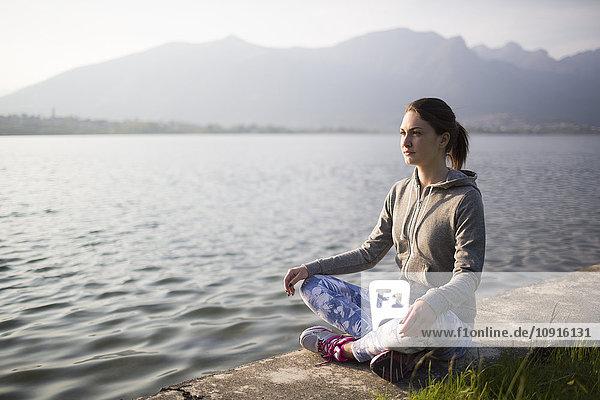 Italien  Lecco  entspannte junge Frau am Seeufer sitzend