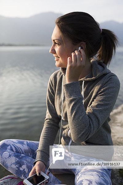 Italien  Lecco  lächelnde junge Frau am Seeufer beim Musikhören