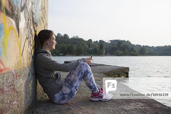 Italien  Lecco  entspannte junge Frau am Seeufer beim Musik hören