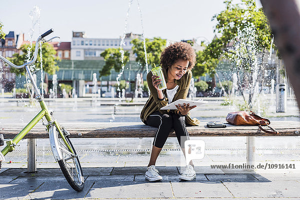 Young woman sitting on a bench with beverage reading notes