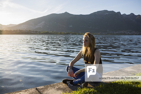 Italy  Lecco  thoughtful teenage girl sitting on the edge of the lake