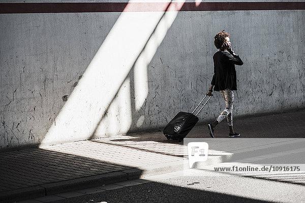 Laufende Geschäftsfrau mit Gepäcktelefonie mit Smartphone