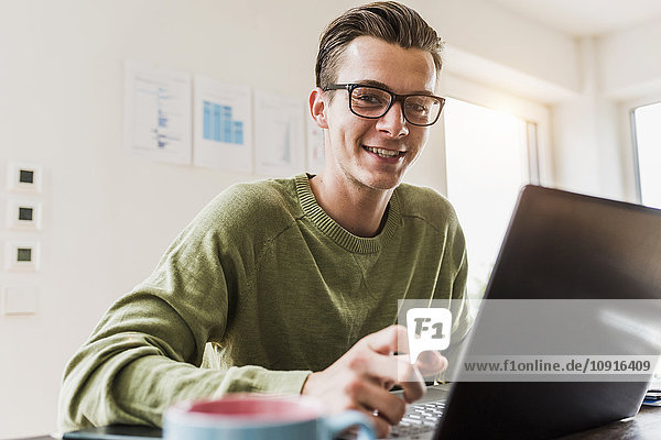Portrait of smiling man at desk with laptop