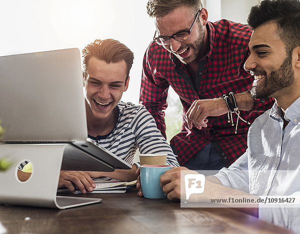 Drei glückliche junge Profis teilen sich den Laptop im Büro