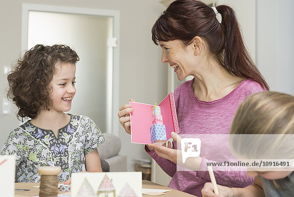 Mother and daughters making greeting cards