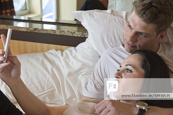 Junges Paar auf Kreuzfahrt im Bett liegend mit Selbstbedienung mit Smartphone