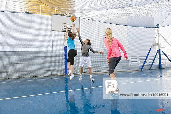 Drei Leute spielen Basketball auf dem Deck eines Kreuzfahrtschiffes.