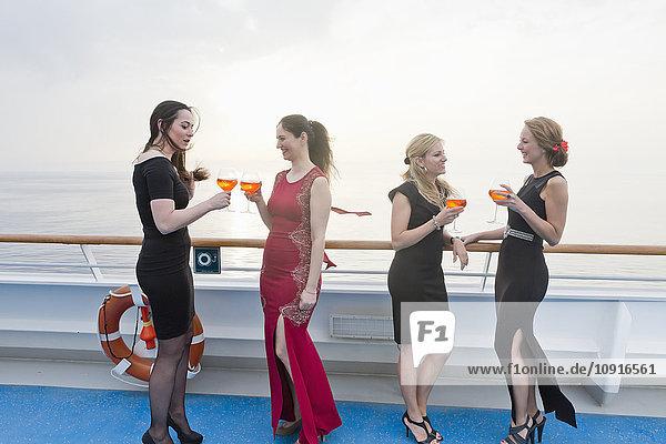 Vier Frauen mit Aperitifs an Deck eines Kreuzfahrtschiffes