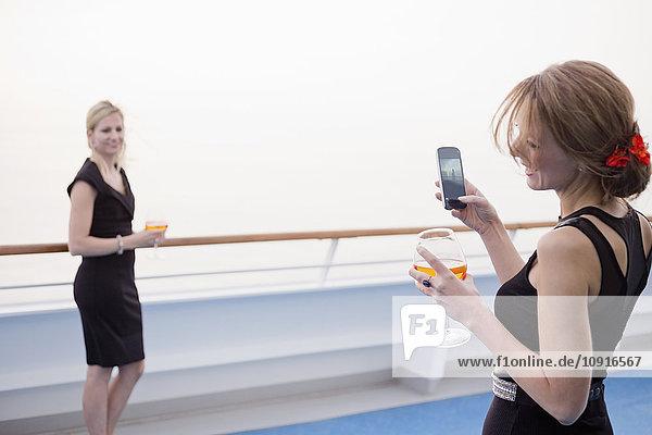Lachende Frau beim Fotografieren ihres Freundes an Deck eines Kreuzfahrtschiffes