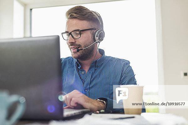 Mann mit Headset und Laptop im Büro